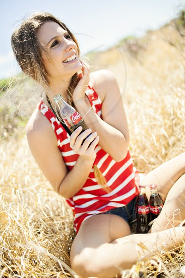 woman wearing a red and white striped tank top holding a glass coke bottle photo