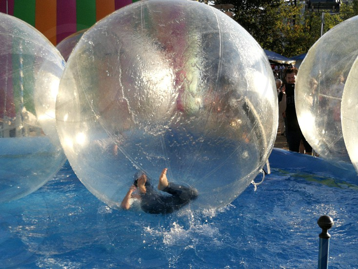 human inside a inflatable ball on a swimming pool photo