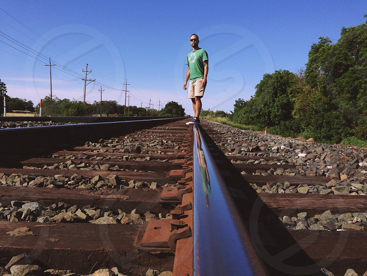 man wearing green t shirt standing on railroad tracks photo