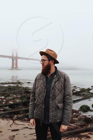 man in grey bubble jacket standing on the shore near golden gate bridge photo