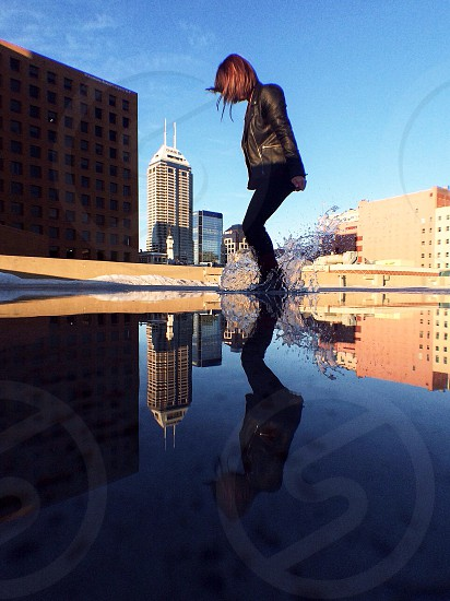 woman in black pants playing on water photo