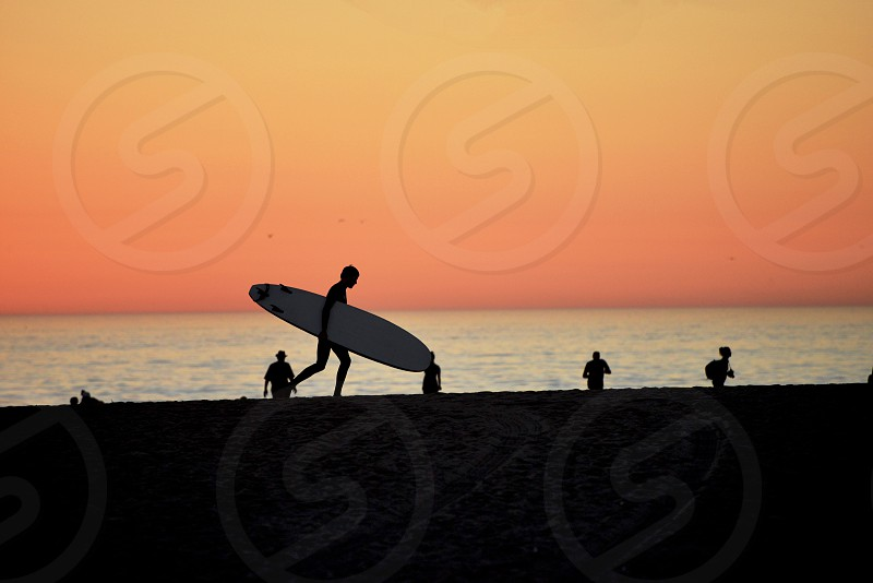silhouette of person carrying surfboard walking by the beach during orange and red sunset photo