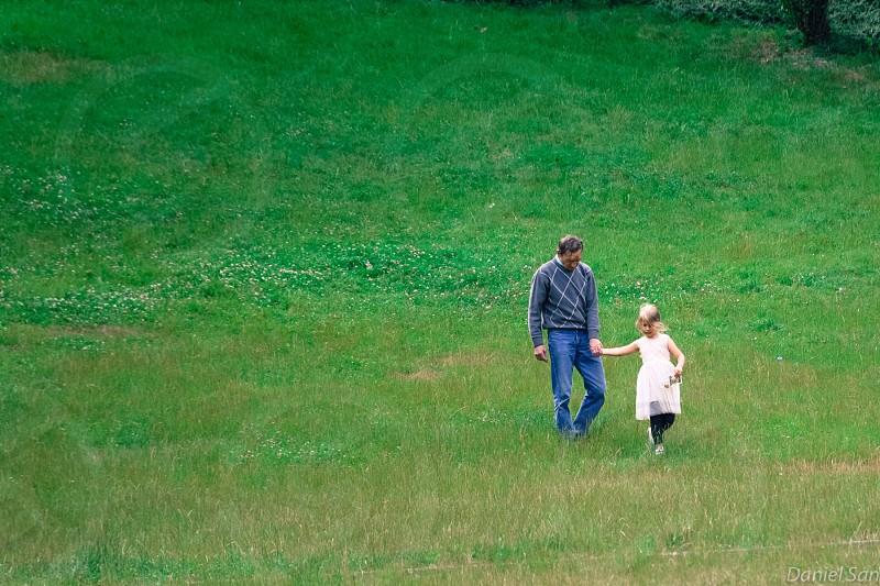 man in grey crew neck sweater holding girl in white tank dress in green field during daytim photo