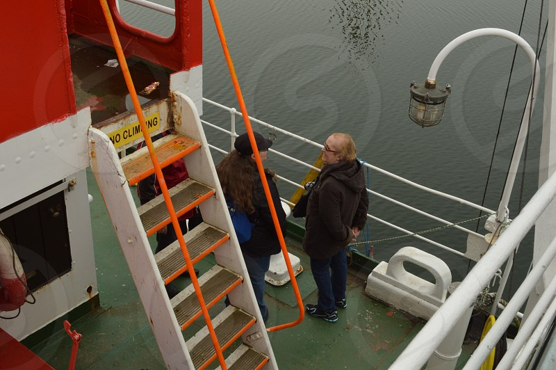 Two ladies talking while standing between the railing and a ladder on the deck of a boat. photo