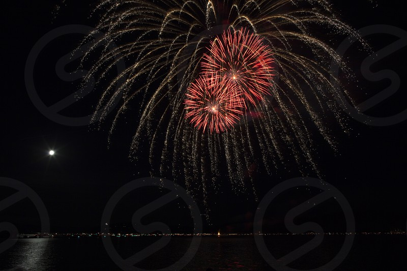 Each year Coeur d'Alene hosts a spectucular fireworks display in celebration of 4th of July. Some of the images in this series  also capture the full moon making its mark in the night sky. This year we were fortunate to experience a calm night. This was a family event to remember! photo