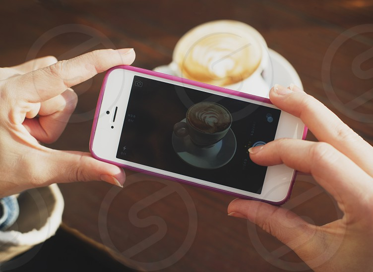 Female hands holding mobile iphone taking pictures of coffee espresso photo
