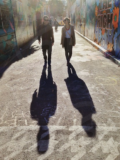man and woman walking on gray cement road photo