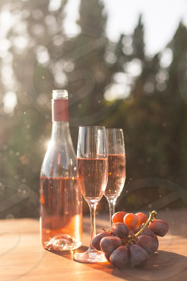 two champagne flutes filled with rose wine on a table next to the bottle and purple table grapes under the sun photo