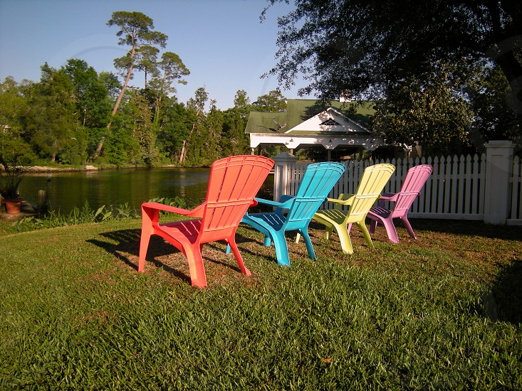 Four solid color adirondack style lounging chairs on lawn by lake photo