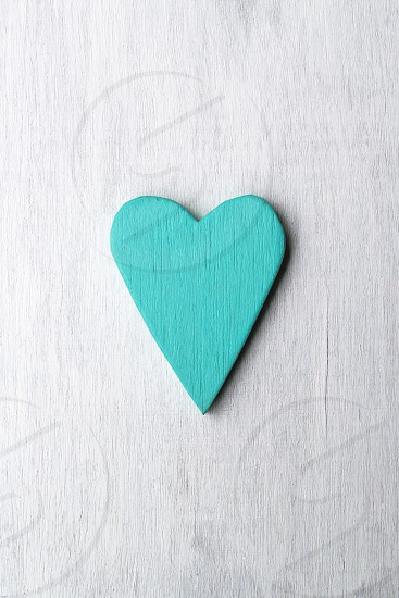 turquoise painted wooden heart on white wooden background photo