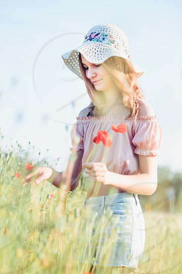Beautieful young girl in the field of wild flowers. Teenage girl picking the spring flowers in the meadow wearing hat and summer clothes. Spending time close to nature photo
