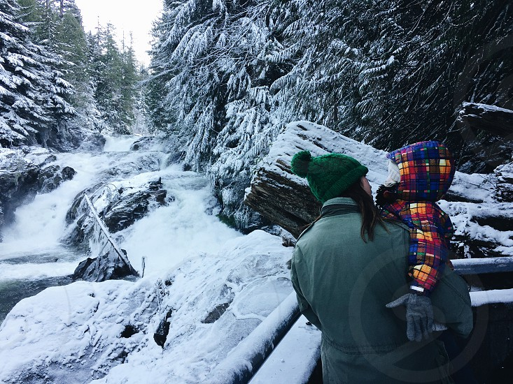 woman and child in winter apparel near snowy waterfall photo