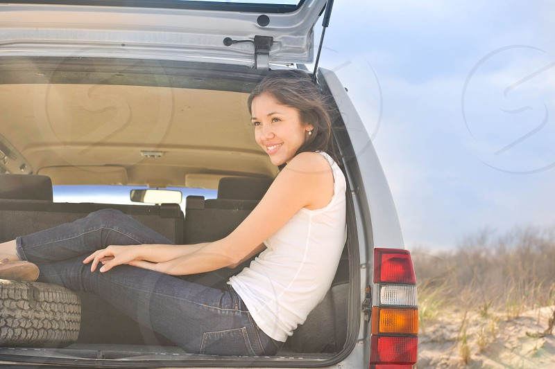 woman sitting on the back of the car photo