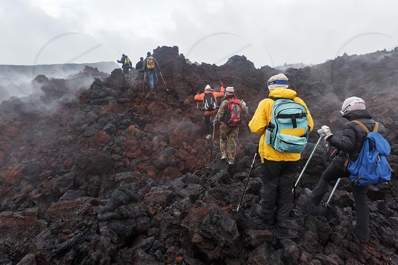 TOLBACHIK VOLCANO KAMCHATKA PENINSULA RUSSIAN FAR EAST - JULY 27 2013: Group of tourists hiking on the lava field eruption Tolbachik Volcano on Kamchatka Region (Klyuchevskaya Group of Volcanoes). photo