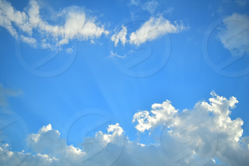 clouds against blue sky with sun beams photo