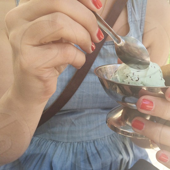 woman holding stainless steel spoon and cup of ice cream photo