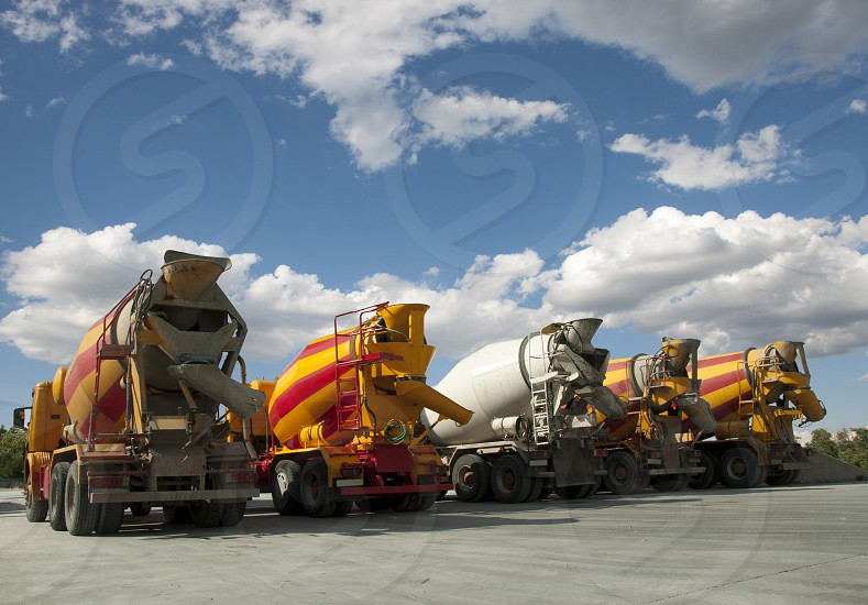 Five Cement Trucks on blue sky photo