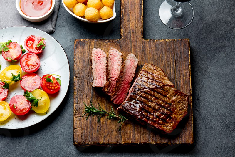 Sliced grilled medium rare beef steak served on wooden board Barbecue bbq meat beef tenderloin. Top view slate background. photo