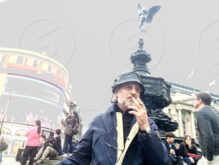 A man smoking a cigar in London London square London icon  photo