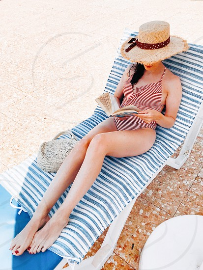 girl straw hat swimsuit reading a book leisure relax relaxing vacation summer summertime summer lifestyle relaxing moments womenswear photo