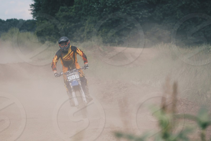 A man on a motorcycle viewed through the dust of a motocross track.  photo