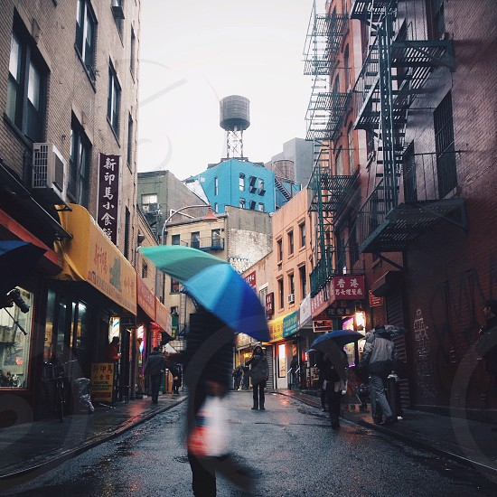 person in black long shirt and pants using blue umbrella photo