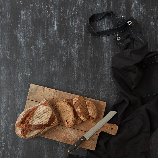 A loaf of rustic bread sliced on a cutting board on a dark background with a knife and a black apron flat lay photo