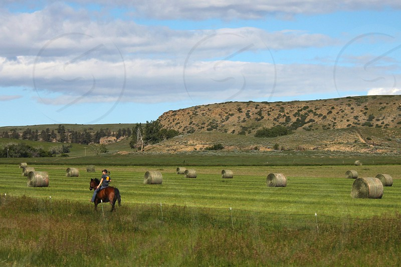 Big sky country horse rider hay bales mountains clouds Montana photo