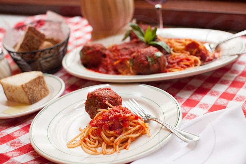 meatball spaghetti on white ceramic plate beside pastry photo