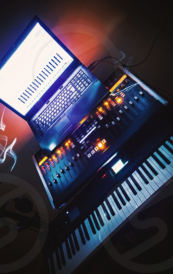 Modern musical equipment mixing console laptop and keyboard.   photo