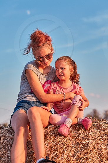Sisters teenage girl and her younger sister playing together on hay bale outdoors spending summer vacation in the countryside. Candid people real moments authentic situations photo