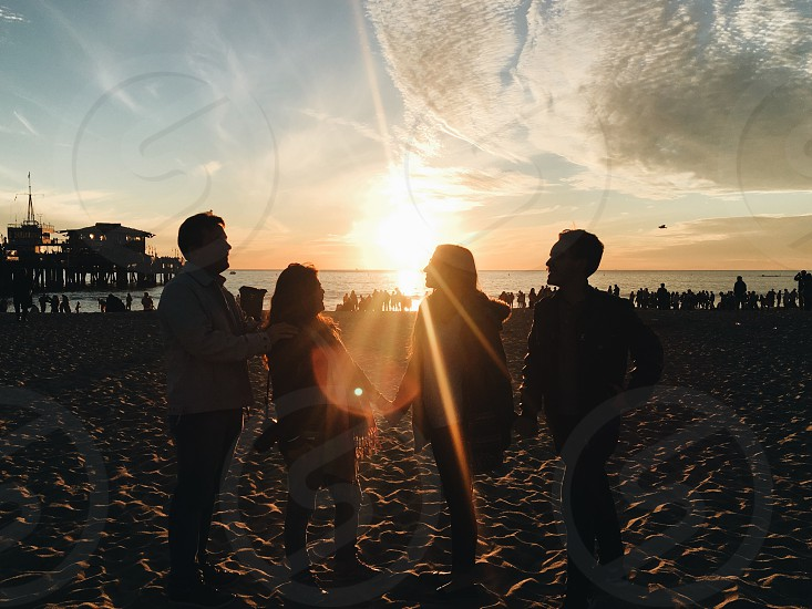 silhouette of four people at beach during golden hour photo