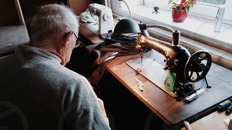 An old tailor sewing. Old vintage sewing machine. photo
