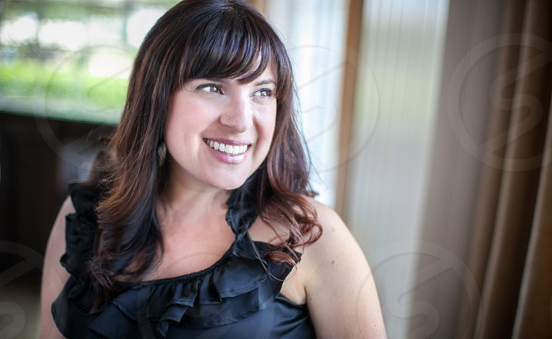 A woman with medium brown hair wearing a semi-formal black top smiles and looks out a large window. photo