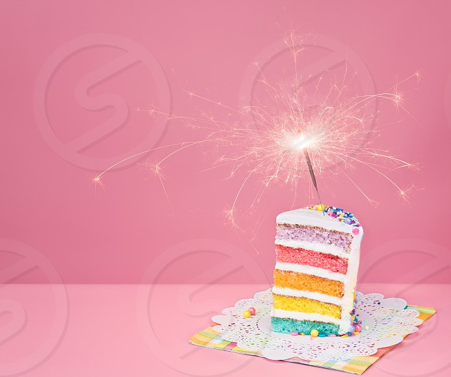 Slice of  birthday cake on a pink background with rainbow layers and sparkler. photo