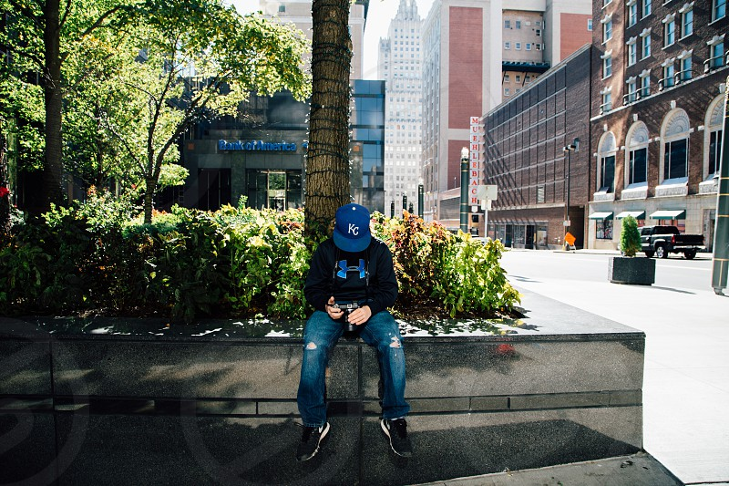 man in black and blue under armour hoodie on concrete ledge in city photo
