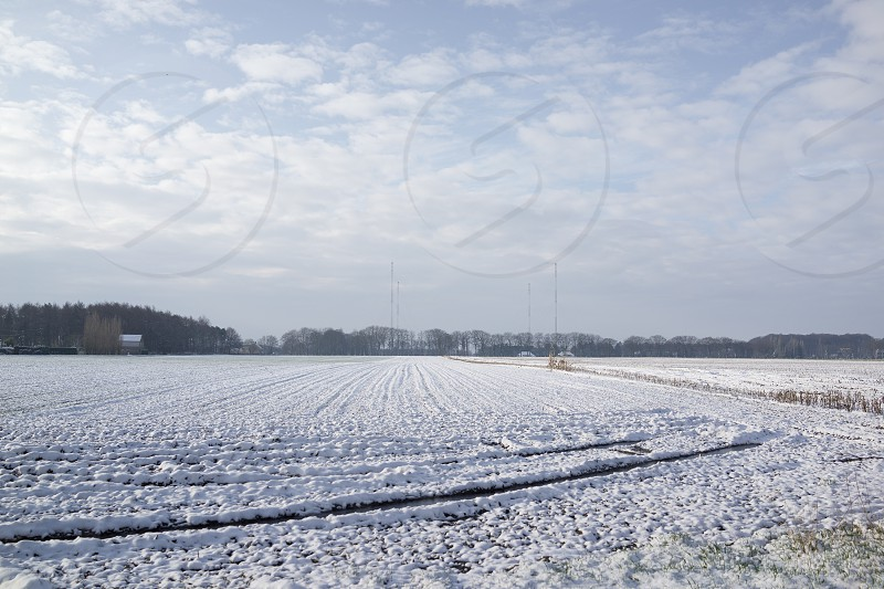 Wide view on a rural field with fresh layer of snow. Distant barn and poles. photo