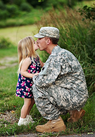 person in army uniform kissing female child photo