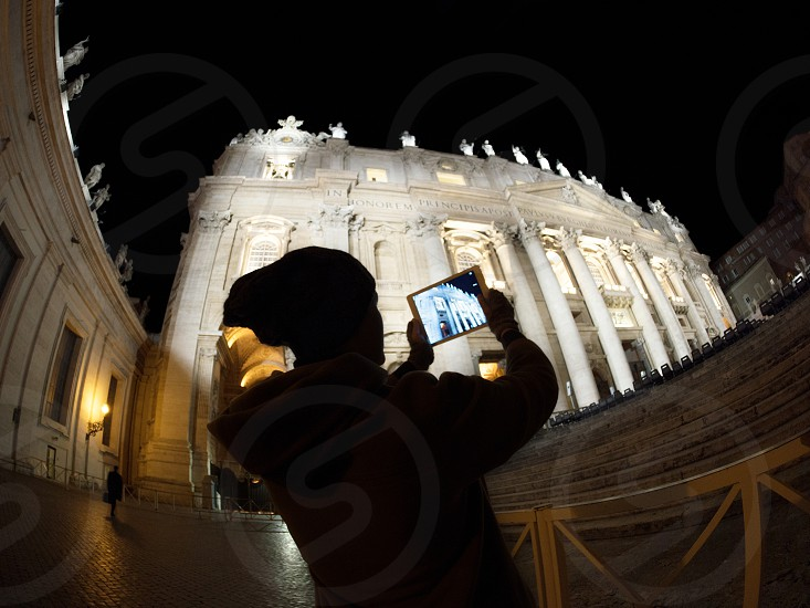 Wide angle shot of a woman silhouette using tablet computer to take photo or make video of St. Peters Basilica in Vatican City. Illuminated historic building photo
