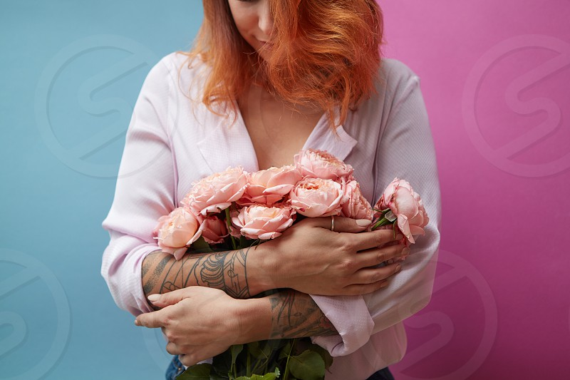 Flowers of pink roses in the hands of a young woman with a tattoo on a double rose against blue background with copy space. Mothers Day photo