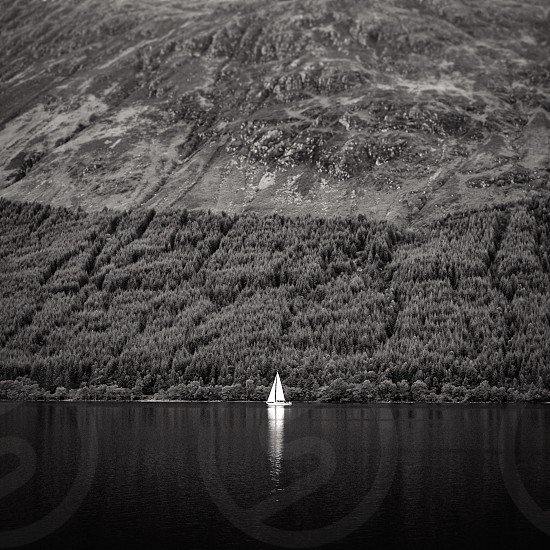 sailing yacht boat Scotland lake river hills mountains water sail small tiny simple minimal minimalistic holiday adventure travel leisure woods forest United Kingdom UK highlands scottish highlands moody magestic nature dark noir black and white sport vacation weekend trip photo