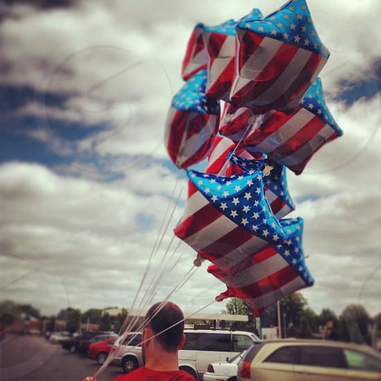 man holding u.s flag printed star shape balloons photo
