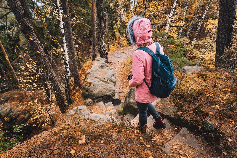 Adult women with backpack on hiking trail in forest. Travel lifestyle adventure concept. photo