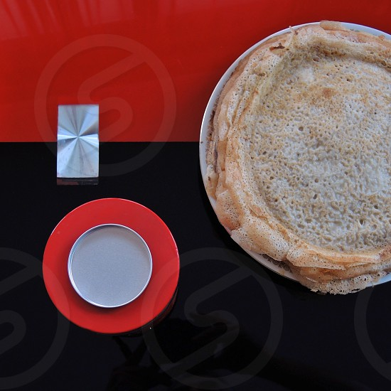 pancake on plate beside red round plastic container photo