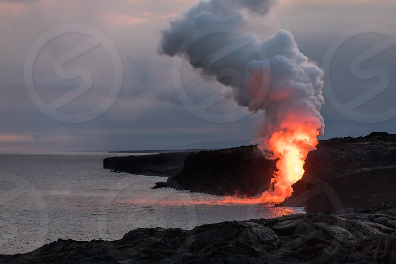 Lava spilling into the ocean from Hawaii Volcanoes National Park on the Big Island of Hawaii at sunset. photo