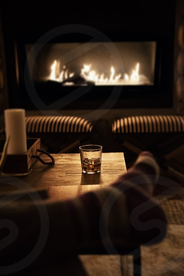 Point of view relaxing by the fire with a whisky on ice drink. photo