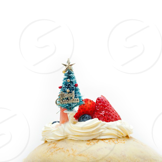 christmas tree on top of a pancake crepe mountain with whipped cream and strawberry photo
