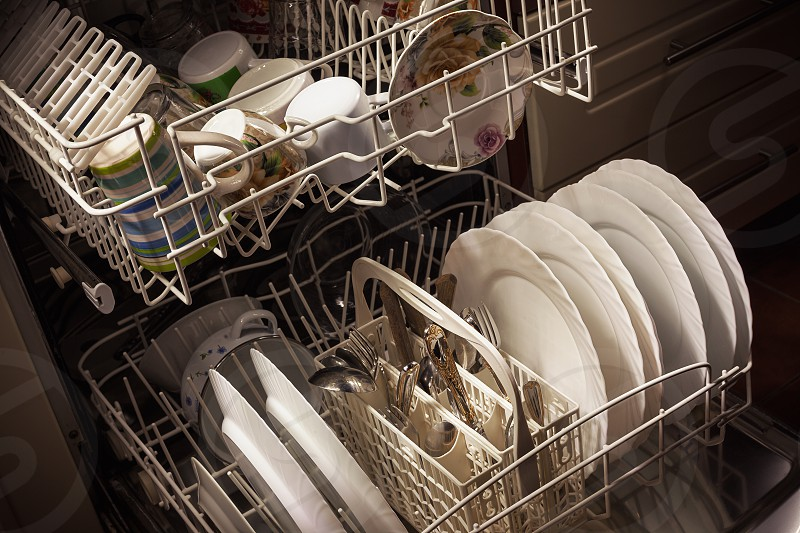 Clean dishes and accessories in dishwasher after washing. photo