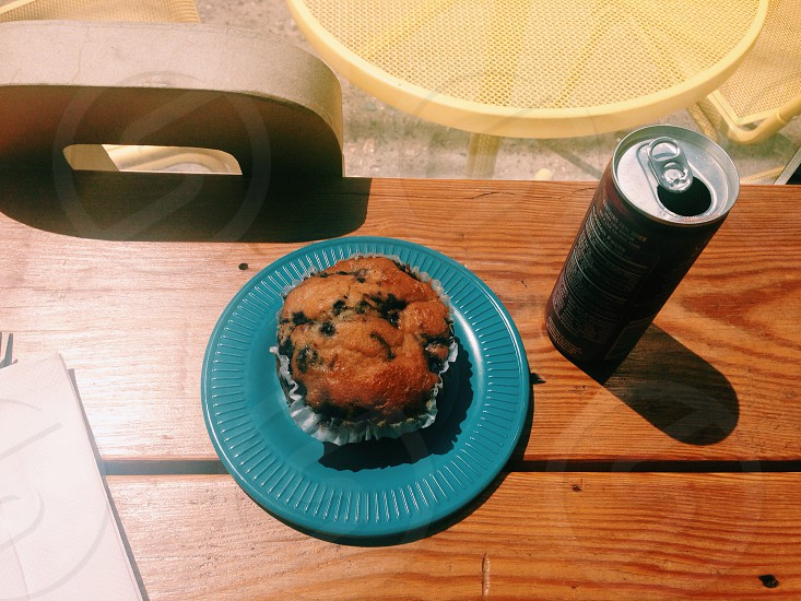muffin on blue plastic plate beside black can on table photo