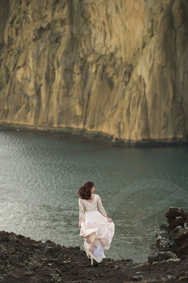 Bride walking down mountain path to water in Iceland photo